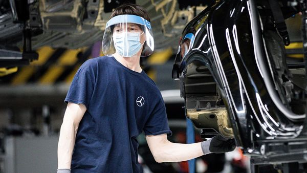 A worker wears a protective face mask and shield on the assembly line inside the Mercedes-Benz AG automobile plant, operated by Daimler AG. (Bloomberg)