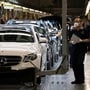 Workers inspect newly assembled cars at a Beijing Benz Automotive Co. Ltd factory, a German joint venture company for Mercedes-Benz, in Beijing.
