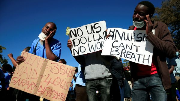 Health workers carry placards as they protest against economic hardship and poor working conditions during the coronavirus disease (COVID-19) outbreak in Harare, Zimbabwe. (REUTERS)