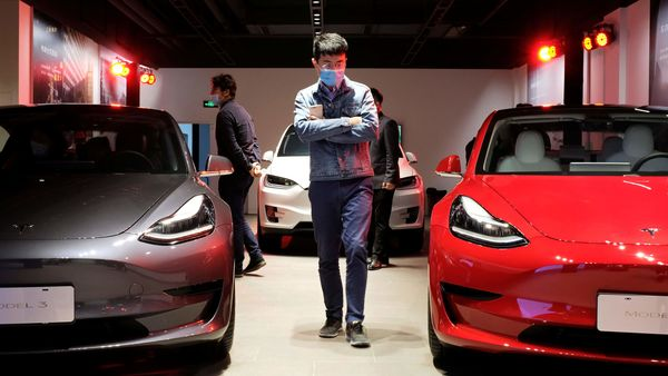 A man wearing a face mask following the coronavirus disease outbreak walks by Tesla Model 3 sedans and Tesla Model X sport utility vehicle at a new Tesla showroom in Shanghai, China. (REUTERS)