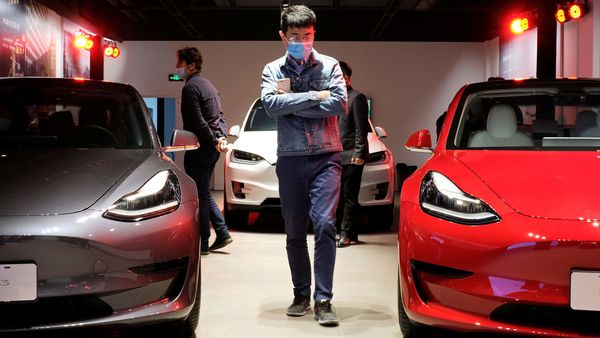A man wearing a face mask following the coronavirus disease (COVID-19) outbreak walks by Tesla Model 3 sedans and Tesla Model X sport utility vehicle at a new Tesla showroom in Shanghai, China May 8, 2020. (REUTERS)