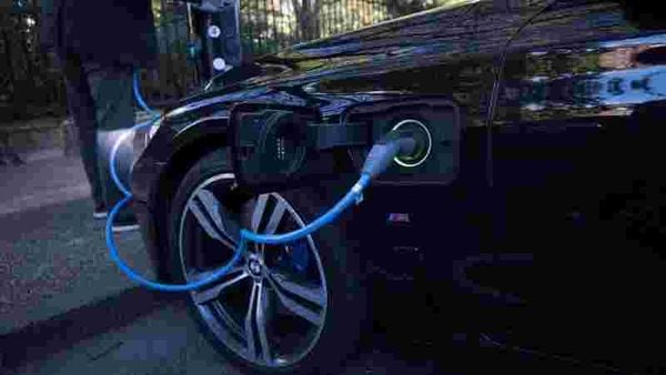 File photo: A driver plugs a cable into a Source power point to charge his electric car in London, Britain. (Image used for representational purpose) (REUTERS)