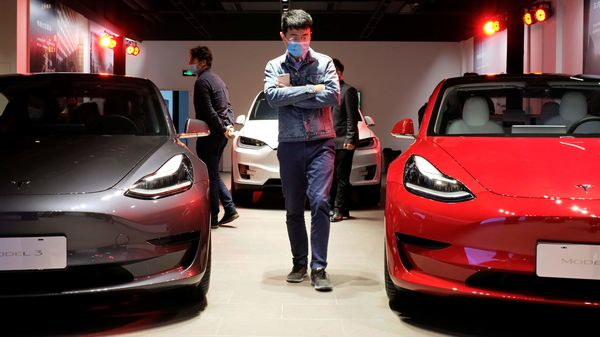 A man wearing a face mask following the coronavirus disease (Covid-19) outbreak walks by Tesla Model 3 sedans and Tesla Model X sport utility vehicle at a new Tesla showroom in Shanghai, China. (REUTERS)