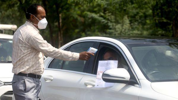A man checks temperature and ID cards of commuters at Delhi-Noida border.