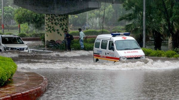 An ambulance wades through a waterlogged road after heavy rains in Noida. (PTI)