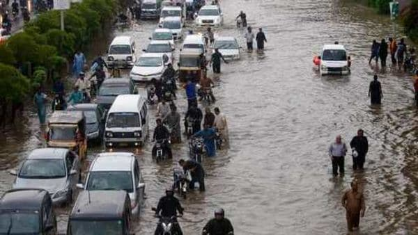 Vehicles drive through a flooded road caused by heavy rainfall in Karachi. (AP)