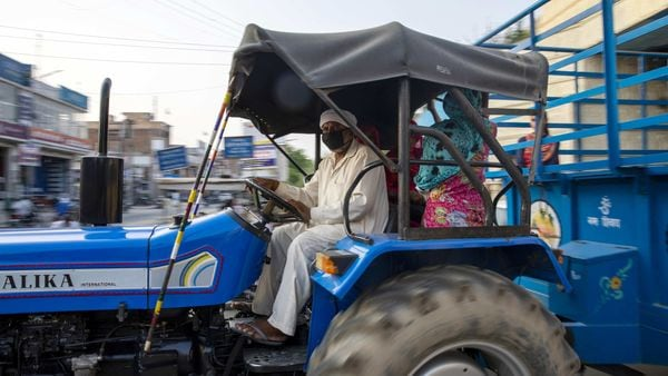 A man wears a protective mask while driving a tractor in Gharaunda, Haryana, India on Friday, June 26, 2020. From March through May, around 10 million migrant workers fled India�s megacities, afraid to be unemployed, hungry and far from family during the world�s biggest anti-Covid lockdown. Migrant workers aren�t expected to return to the cities as long as the virus is spreading and work is uncertain. Photographer: Prashanth Vishwanathan/Bloomberg (Bloomberg)