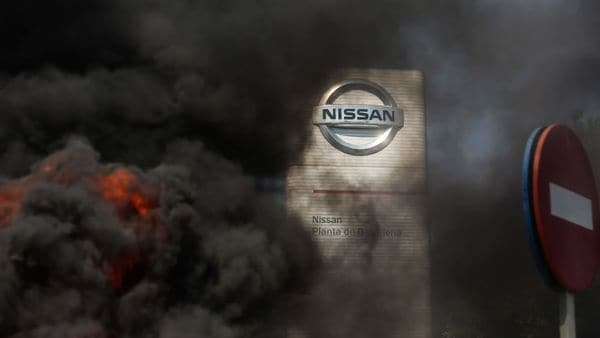 Demonstrators protested outside Nissan's factory against the closure; they burnt tires which caused smoke. (Bloomberg)
