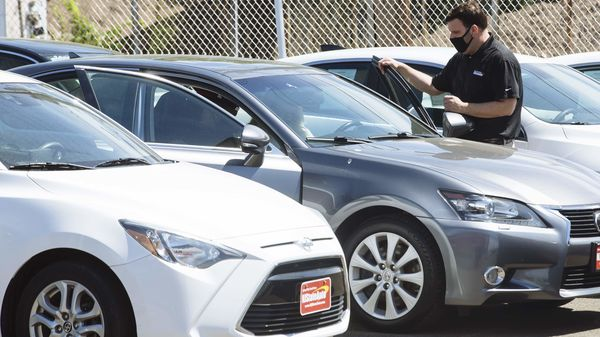 A car dealer wearing a protective mask shows a vehicle to customers at a used car dealership. (Representational photo) (Bloomberg)