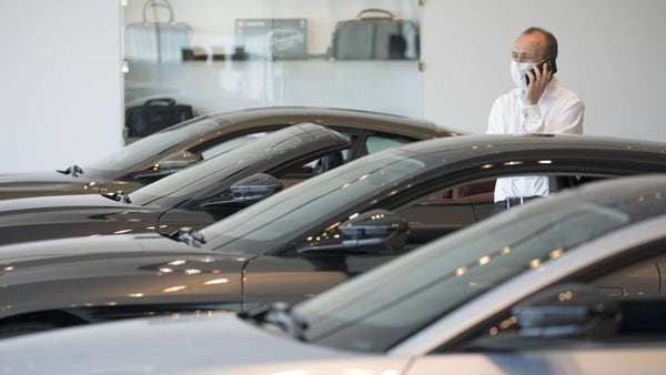 A salesman wearing a protective face mask speaks on a mobile phone at the Aston Martin Works dealership in Newport, UK. (File photo) (Bloomberg)