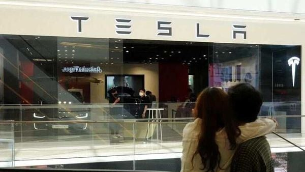 File photo - A couple looks at a Tesla dealership. (Representational Image) (REUTERS)