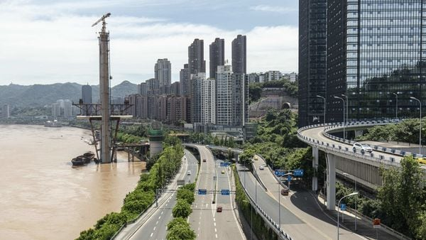 File photo - Vehicles travel over a highway as a bridge stands under construction over the Yangtze River in downtown Chongqing, China. (Bloomberg)