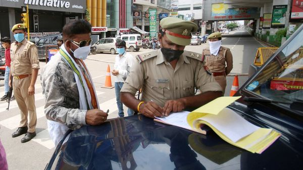 A police personnel fines a commuter in Noida for violating Covid-19 rules.