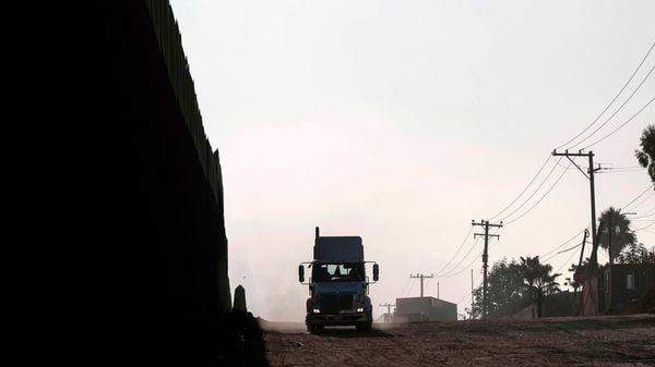 A truck rides along the Mexico-US border fence before lining up to cross to the US at the Otay commercial port of entry in Tijuana, Baja California state, Mexico.