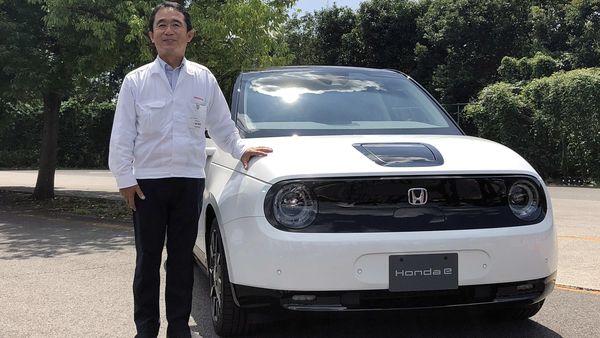 Senior Chief Engineer Tomofumi Ichinose poses for a photograph next to a Honda E electric car. (REUTERS)