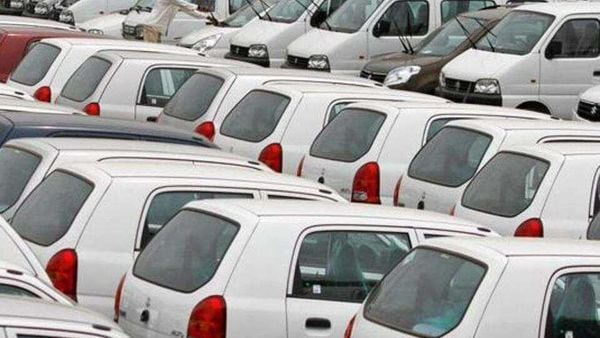 A worker adjusts the windscreen wipers of a parked car at a Maruti Suzuki stockyard. (File photo)