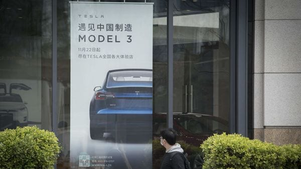 An advertisement for the Tesla Model 3 is displayed at a Tesla dealership in Shanghai. (Bloomberg)