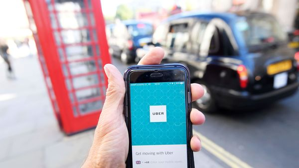 A London taxi passing as the Uber app logo is displayed on a mobile telephone in London. (File Photo) (REUTERS)