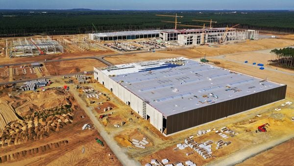 An automobile assembly hall and other partially completed buildings stand on an area of cleared forest land at the Tesla Inc. Gigafactory site in this aerial view in Gruenheide, Germany, on Sunday, Sept. 20, 2020. (Bloomberg)