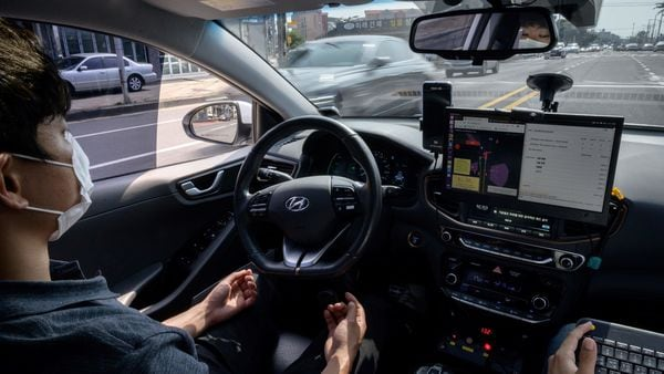 A photo taken on May 28, 2020 shows a safety driver sitting behind the wheel of a Rideflux 'self-driving' car in Jeju. - In a workshop that blends a corporate office with a tool-packed garage, South Korean company Rideflux are looking to take on the multi-billion-dollar giants of Uber, Tesla and Google parent Alphabet with a self-driving car of their own. Their modified Hyundai Ioniq, festooned with cameras and proximity sensors, is the first autonomous vehicle to go into regular service on public roads in the country. (Photo by Ed JONES / AFP) / TO GO WITH: SKorea-automobile-transport-technology, FOCUS by Kang Jin-kyu (AFP)