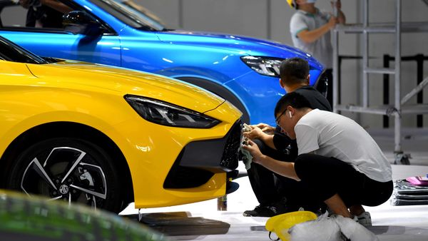 Workers clean a car on the MG stand ahead of the Beijing Auto Show. (AFP)
