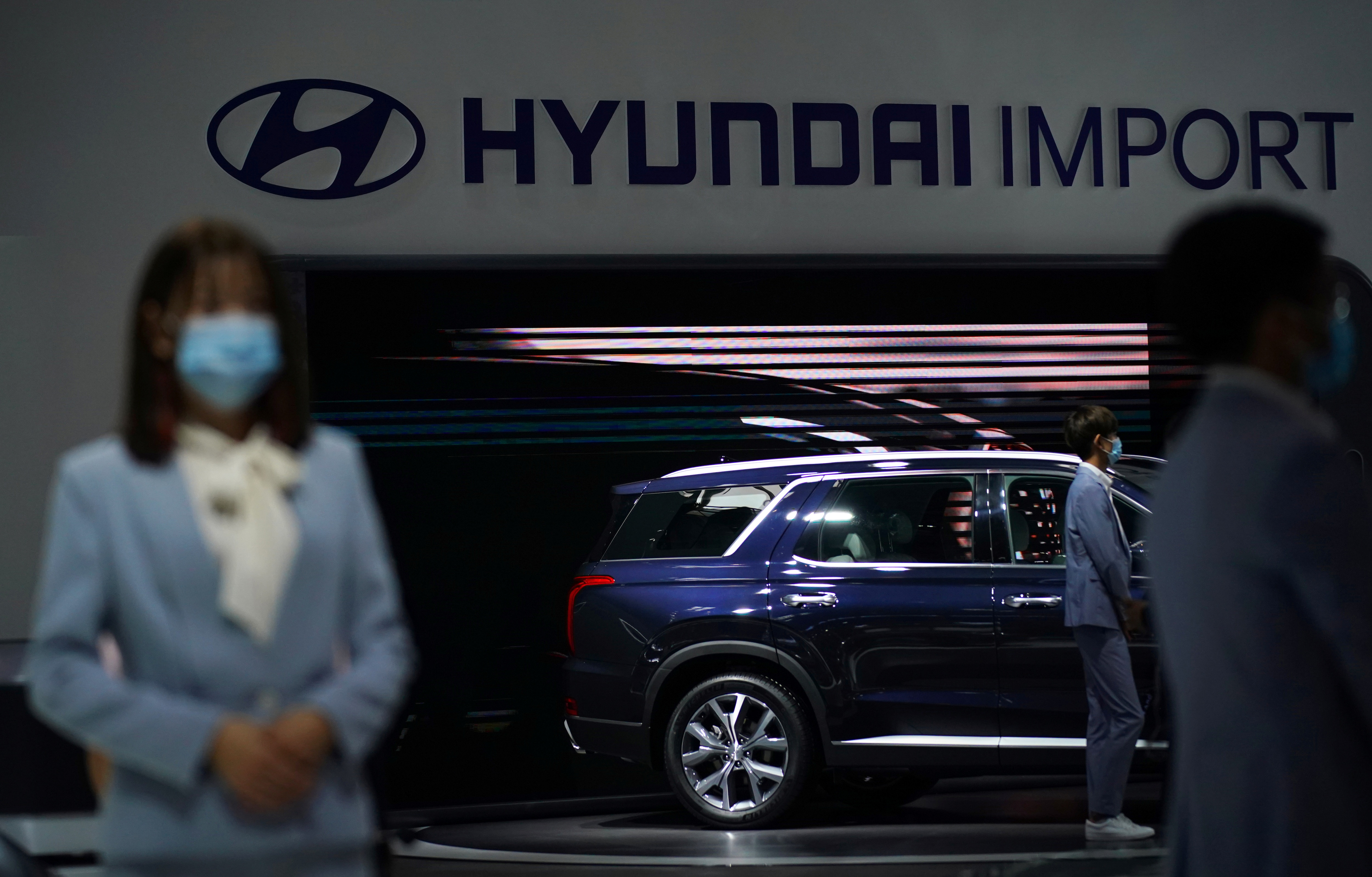 Staffers wearing face masks are seen at a Hyundai booth. (REUTERS)