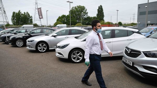 File photo for representational purpose - A car sales person wearing a face mask and gloves walks past vechiles parked on the forecourt of a recently re-opened Vauxhall car dealership in north London. (AFP)