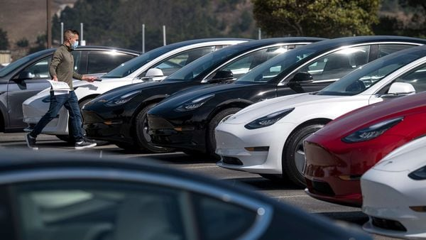 A person wearing a protective mask walks in front vehicles at a Tesla store in Colma, California. (Bloomberg)