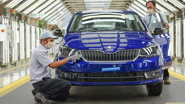 Representational image of Skoda factory workers doing final assessments on a Skoda Rapid.