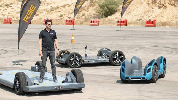REE Automotive CEO Daniel Barel seen standing on one of the three next-gen EV platforms on track.