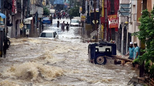 File Photo of floodwater gushes through a street following heavy rains, at Falaknuma, in Hyderabad. (PTI)