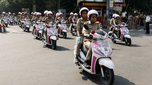 Women police personnel with Pink Patrol vehicles passing from Hazratganj crossing after the Flag off by Uttar Pradesh Governor Anandiben Patel under the Safe City project, a women's safety campaign, in Lucknow on Saturday. (ANI Photo)