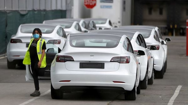 A worker exits a Tesla Model 3 electric vehicle at Tesla's primary vehicle factory in Fremont, California. (File Photo) (REUTERS)