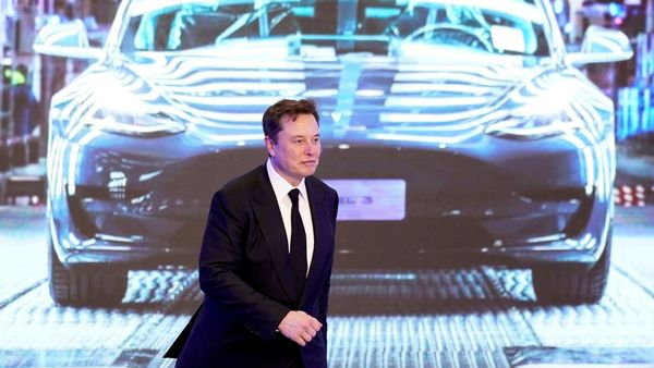 Tesla Inc CEO Elon Musk walks next to a screen showing an image of Tesla Model 3 car during a ceremony. (File Photo) (REUTERS)