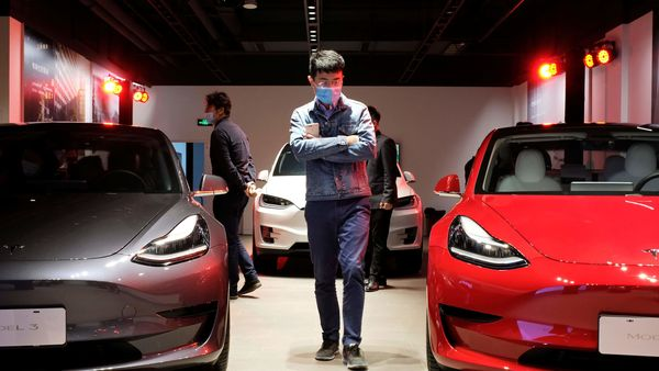 File photo: A man wearing a face mask following Covid-19 outbreak walks by Tesla Model 3 sedans and Tesla Model X sport utility vehicle at a new Tesla showroom in Shanghai. (REUTERS)