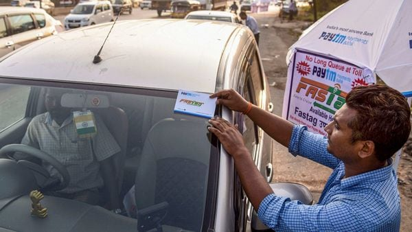 File photo - A worker fixes a FASTag sticker on the windscreen of a car, at Vashi Toll Plaza on Sion Panvel Highway, Mumbai. (PTI)