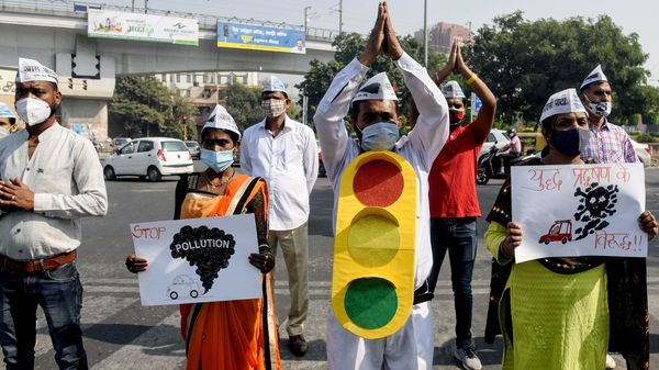 AAP workers hold placards as they urge people to turn off the engines of their vehicles while waiting at traffic signals.