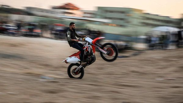 A young Palestinian rides his motorcycle on a sandy hill during a weekly show in the Al-Zahra area, near Gaza City. (AFP)