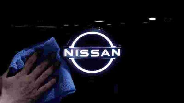 A man wipes the brand logo of Nissan Motor on the front nose section of the company's new Ariya all-battery SUV. (File photo) (REUTERS)