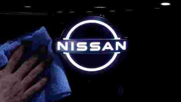 FILE PHOTO: A man wipes the brand logo of Nissan Motor on the front nose section of the company's new Ariya all-battery SUV (REUTERS)