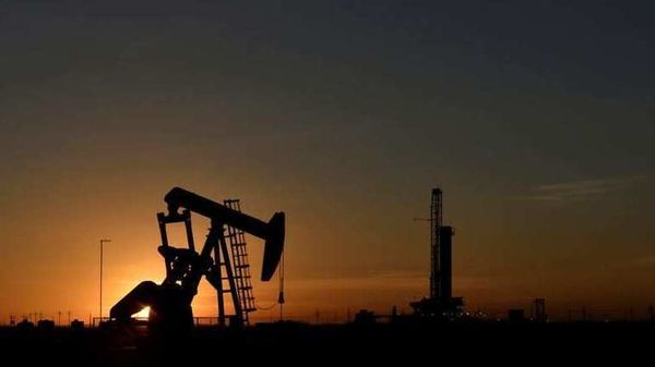 A pump jack operates in front of a drilling rig at sunset in an oil field in Midland, Texas. (REUTERS)