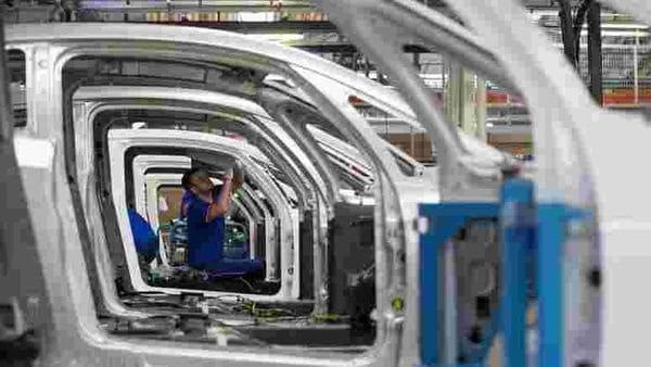 An employee works on the automobile assembly line of Bluecar electric city cars at Renault car maker factory in Dieppe, western France. (REUTERS)