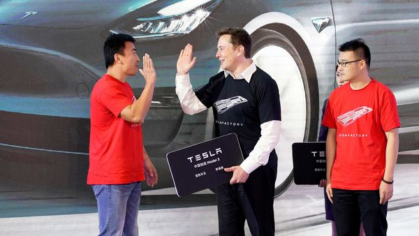 File photo - Tesla Inc CEO Elon Musk poses with Tesla China-made Model 3 vehicle owners. (REUTERS)