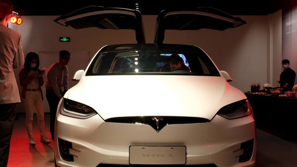 People wearing face masks following the coronavirus disease outbreak check a Tesla Model X sport utility vehicle at a new Tesla showroom in Shanghai, China. (REUTERS)