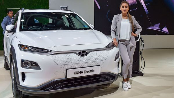 A model poses next to a Hyundai Kona Electric car displayed at the Auto Expo 2020 in Greater Noida. (File photo) (PTI)