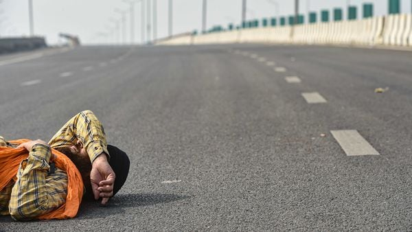 A farmer sleeps on the road on NH-24 during protests against the new farm laws, at Ghazipur border in New Delhi. (PTI)