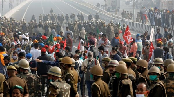 Farmers block a highway as police officers stand guard during a nationwide strike against the newly passed farm bills at the Delhi-Uttar Pradesh border in Ghaziabad, India, December 8, 2020. REUTERS/Adnan Abidi (REUTERS)