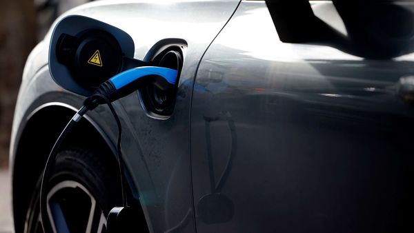 A charging cable is pictured plugged into a Volvo electric vehicle (EV), parked in a parking bay reserved for electric vehicles, in London on November 18, 2020. - Britain will ban petrol and diesel vehicle sales from 2030 as part of a 10-point plan for a