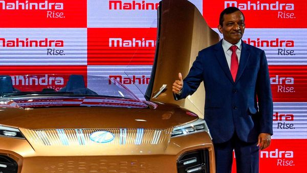 Managing Director (MD) of Mahindra and Mahindra Limited, Pawan Goenka (R), poses with the Mahindra Funster electric concept vehicle at the Auto Expo 2020. (File photo) (AFP)