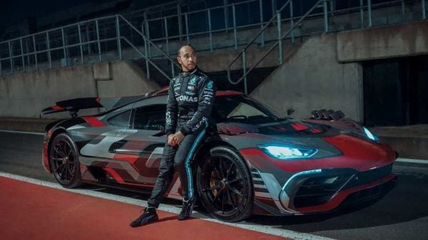 Lewis Hamilton strikes a pose next to a Mercedes AMG-One hypercar.